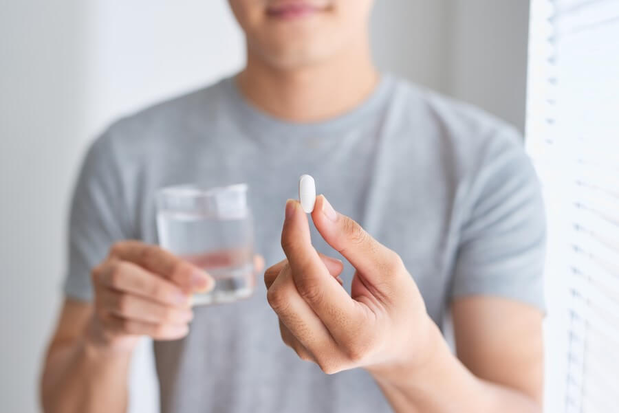 Mężczyzna trzyma szklankę wody i tabletkę paracetamolu.