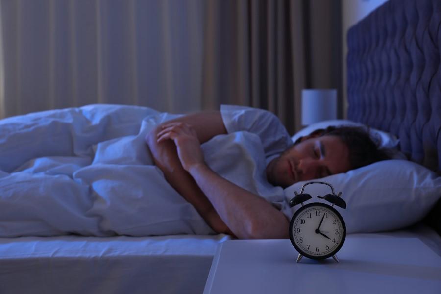 Mężczyzna śpi w łóżku, na stoliku nocnym na ustawiony budzik.