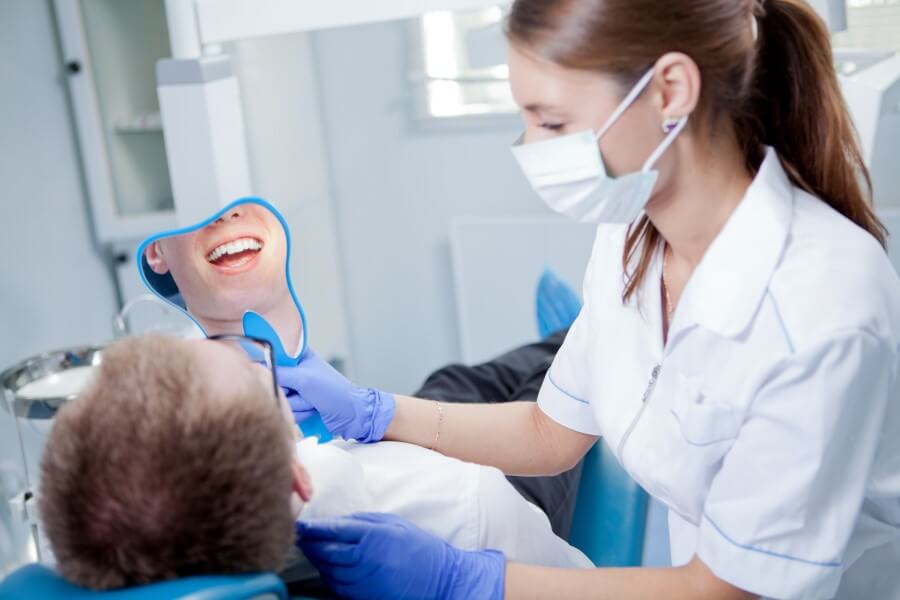 Pacjent u stomatologa, po piaskowaniu zębów ogląda efekty czyszczenia w lusterku.