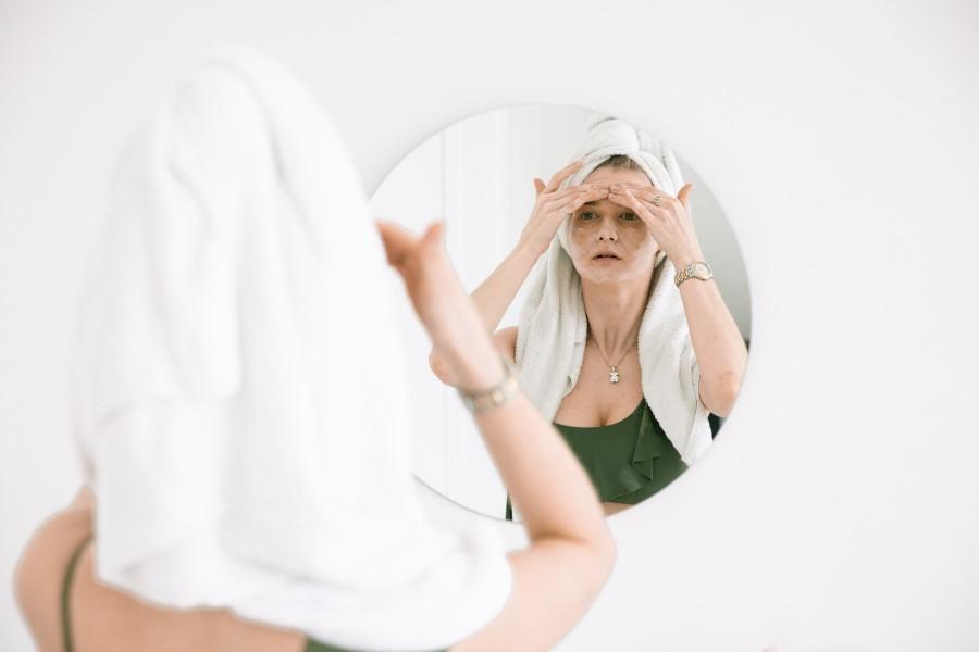 Kobieta po kąpieli nakłada na twarz kosmetyki pielęgnacyjne.