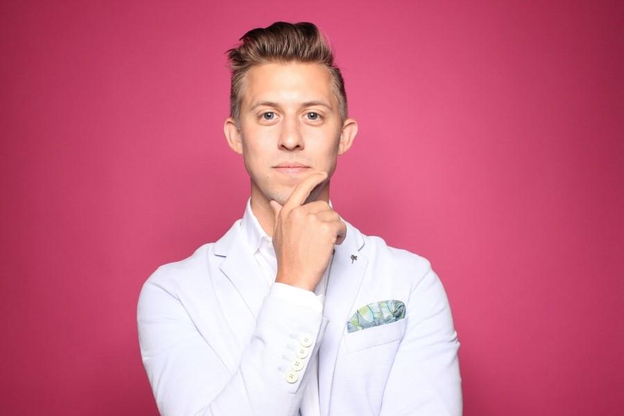 Młody mężczyzna w białym kitlu na różowym tle.