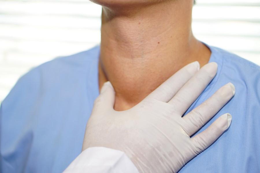 Lekarz bada u pacjenta przerost tarczycy.