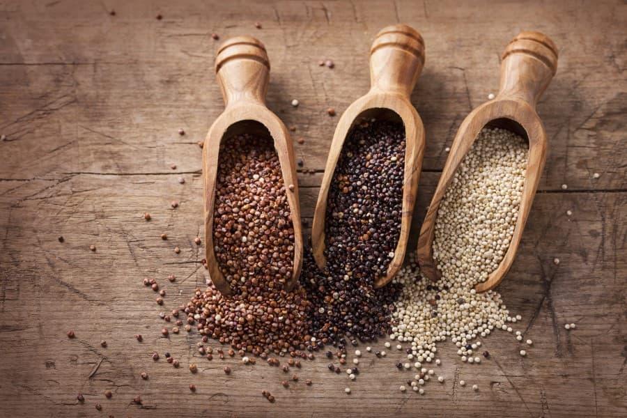 Trzy rodzaje quinoa (komosy ryżowej) w drewnianych łopatkach i częściowo rozsypane na blacie.