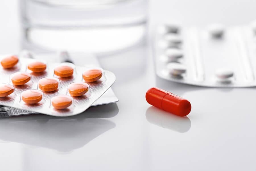 Czerwona kapsułka i tabletki w blistrach leżące na blacie. W tle szklanka wody.