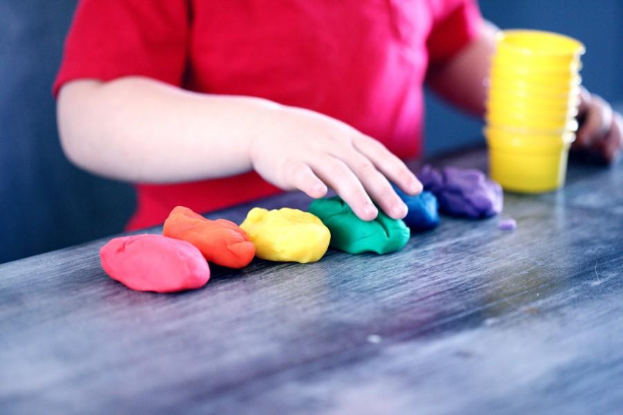 Dziecko bawiące się kolorową masą plastyczną.