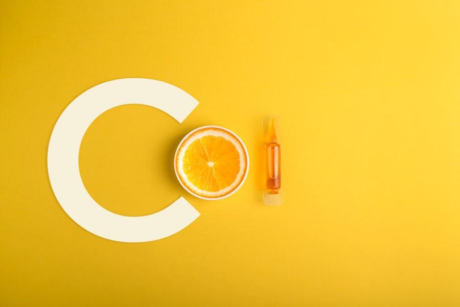 Żółte tło. Litera C, przepołowiona pomarańcza i fiolka serum z witaminą C.