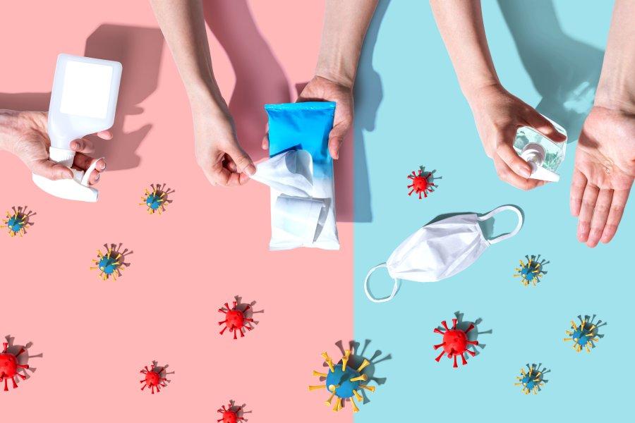 Różowo-niebieskie tło, na tle maseczka ochronna, cząsteczki wirusa oraz dłonie podczas dezynfekcji.