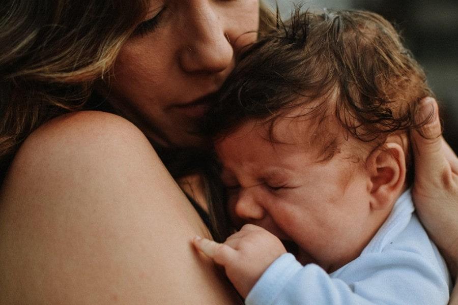 Kobieta trzyma na rękach i tuli płaczące niemowlę.