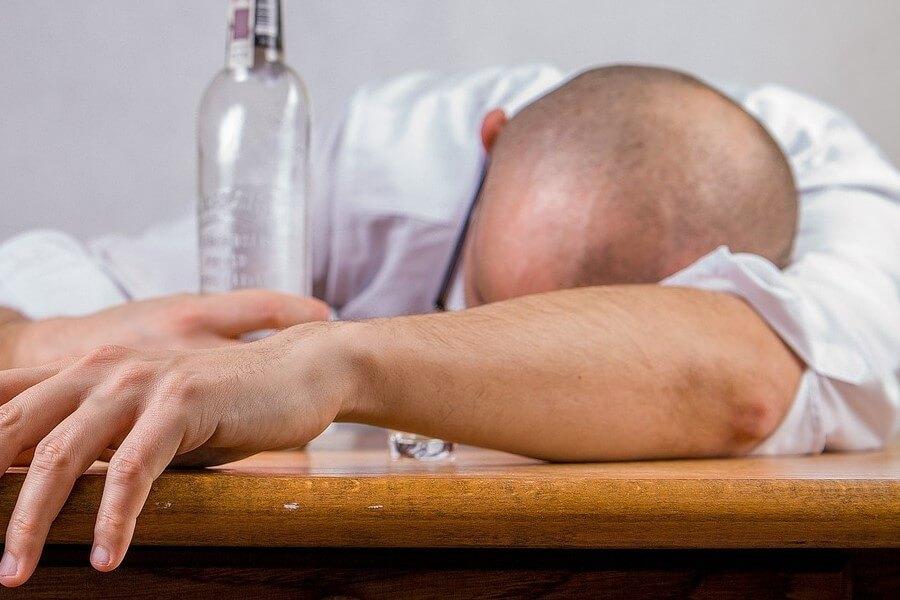 Mężczyzna pod wypływem alkoholu, opiera głowę o blat stołu. Ręką trzyma butelkę z alkoholem.