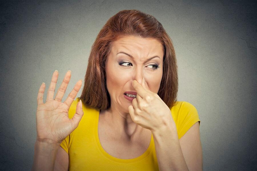 gazy i wzdęcia - kobieta zatyka nos
