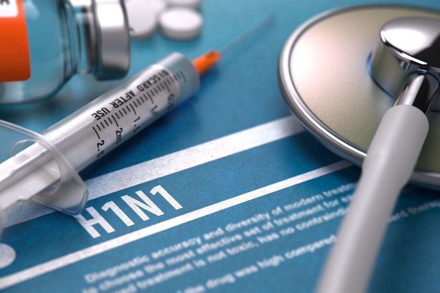 Strzykawka i stetoskop na niebieskiej kartce z napisem H1N1 (wirus świńskiej grypy).