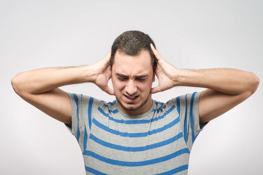 Mężczyzna słyszy szum w uszach, trzyma się dłońmi za głowę, ma grymas na twarzy.