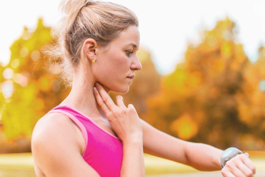 Ubrana na sportowo kobieta przed biegiem w parku mierzy swoje tętno spoczynkowe na tętnicy szyjnej.