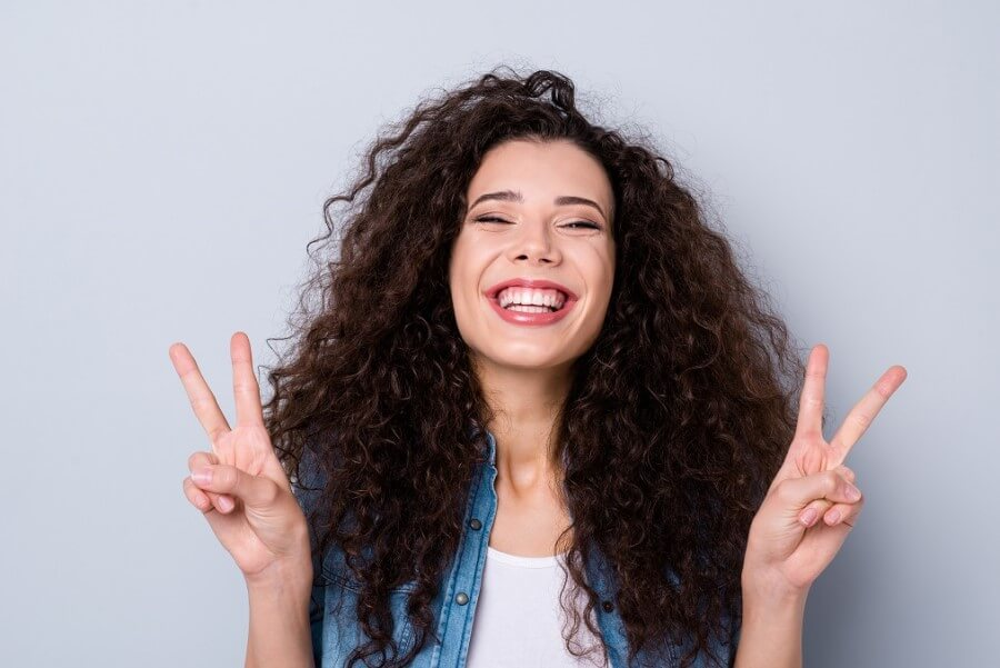 Kobieta z gęstymi, kręconymi włosami. Uśmiecha się i pokazuje dłońmi gest wiktorii.
