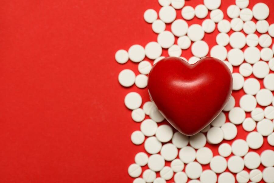 Białe tabletki na czerwonym tle. Na tabletkach leży czerwona figurka serca.