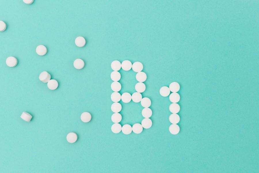 Białe tabletki na niebieskim tle, ułożone w nazwę witaminy B1.