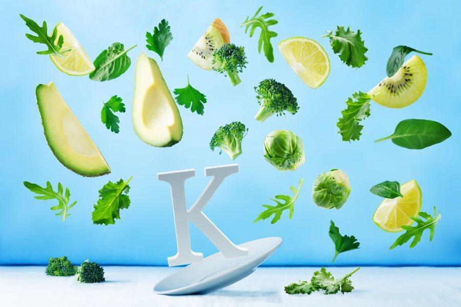 Symbol witaminy K oraz warzywa i owoce będące jej źródłem w diecie.