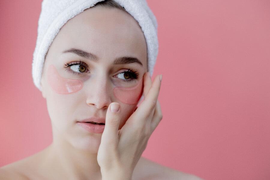 Kobieta po kąpieli, z ręcznikiem na głowie. Nakłada specjalne płatki niwelujące worki pod oczami.