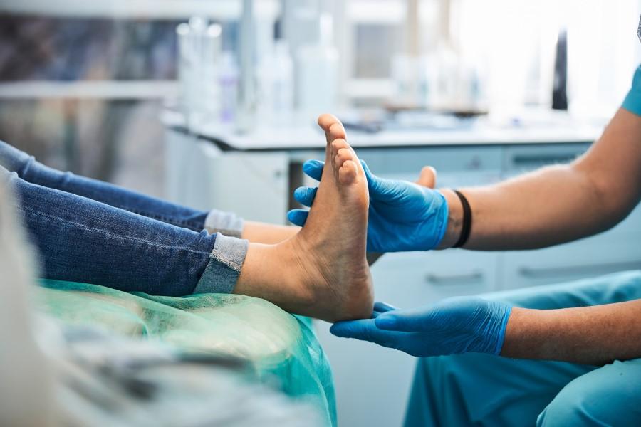 Lekarz bada stopy pacjenta.
