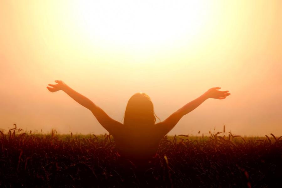Kobieta stoi na polu pszenicy, na tle zachodzącego słońca, wyciąga ręce ku górze.