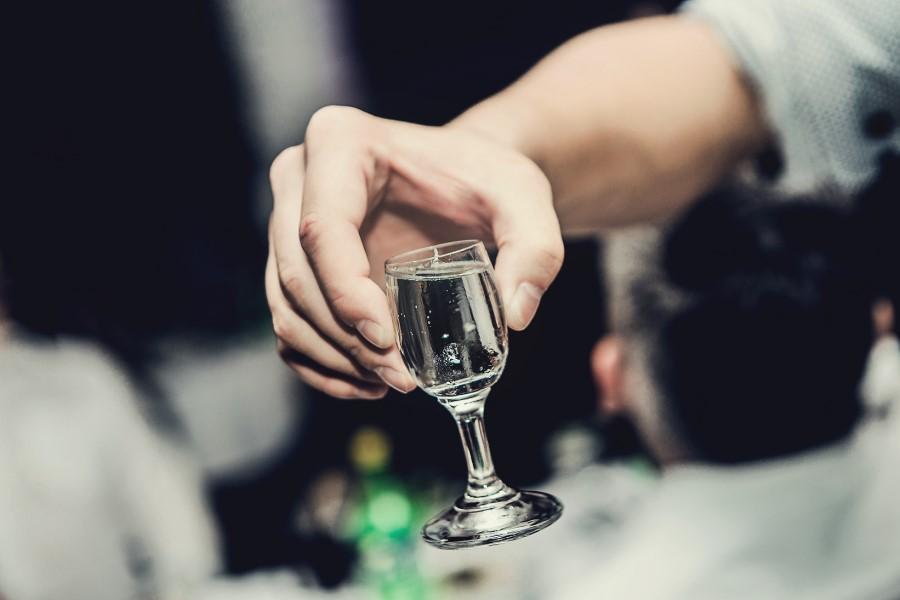 Mężczyzna trzyma w dłoni kieliszek mocnego alkoholu.