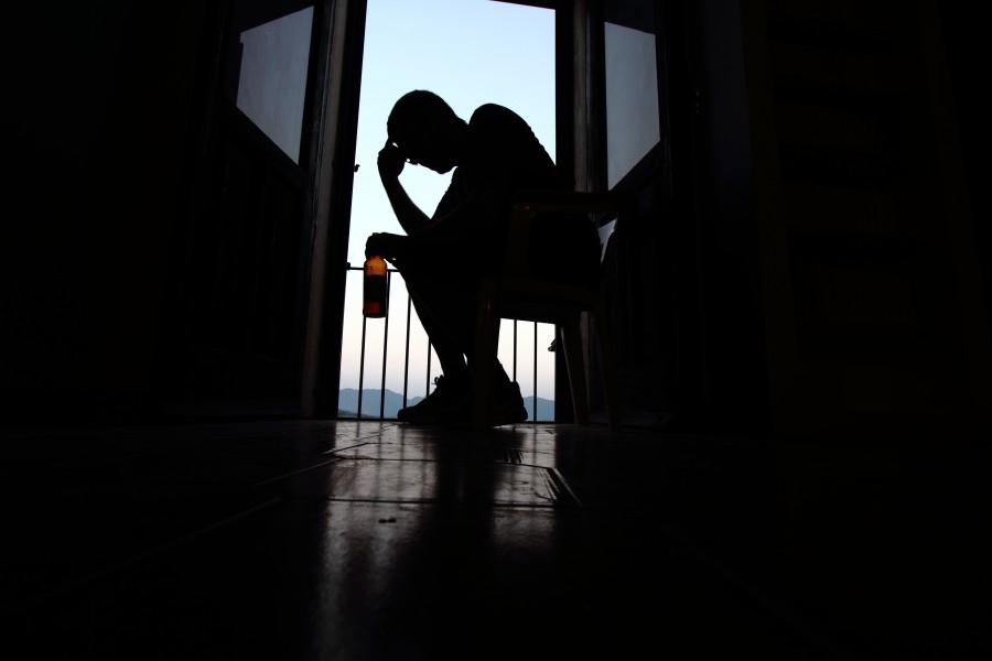 Zmartwiony mężczyzna z butelką piwa siedzi na balkonie