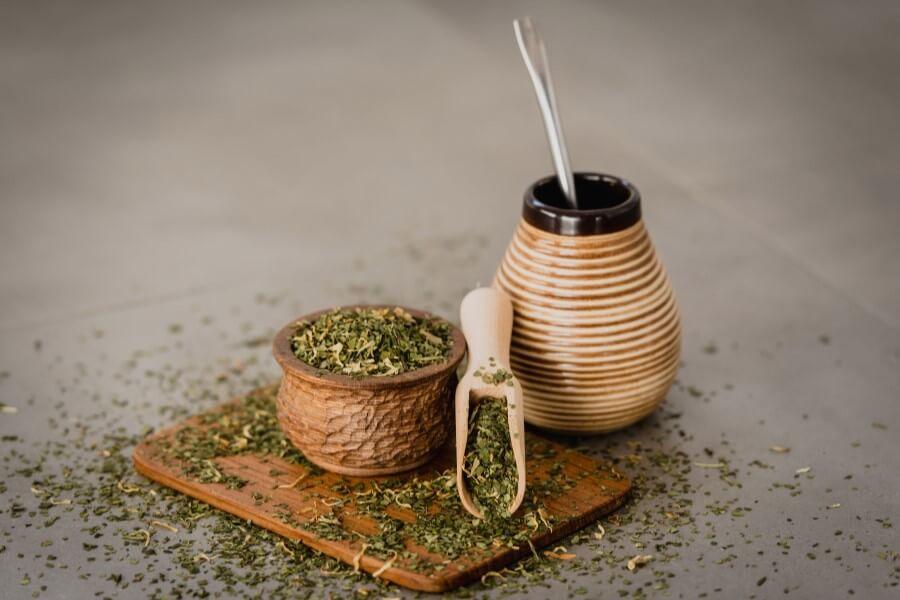Susz yerba mate na drewnianej desce oraz matero z bombillą i gotowym naparem z yerby.