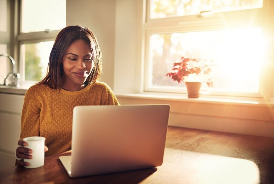 Kobieta robi zakupy online w swoim mieszkaniu, popijając kawę.
