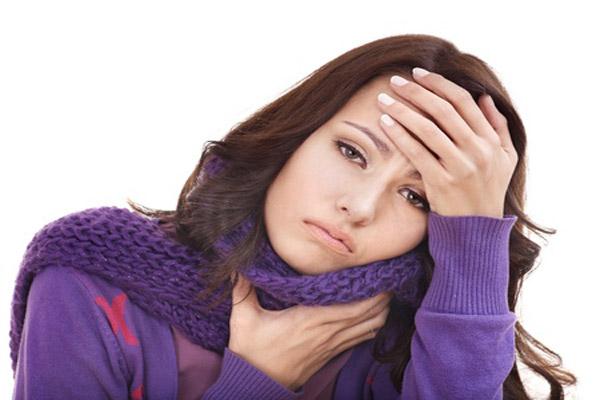przeziębiona kobieta trzymająca się za głowę