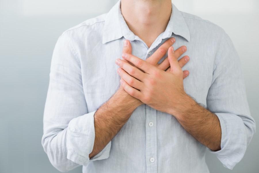 Mężczyzna w białej koszuli, jego dłonie są skrzyżowane na klatce piersiowej, w okolicy serca.