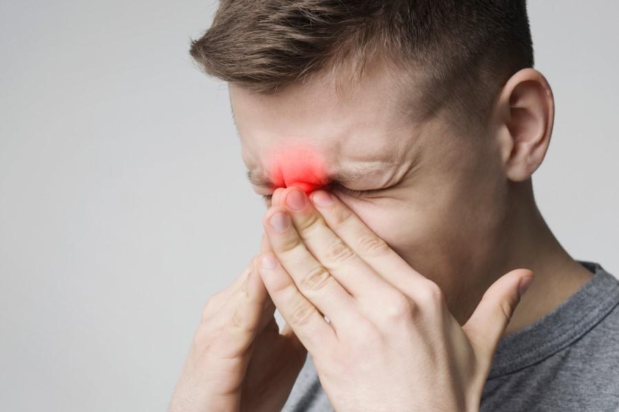 Mężczyzna trzyma się za okolicę nosa. Odczuwa ból, gdyż cierpi na zapalenie zatok przynosowych.