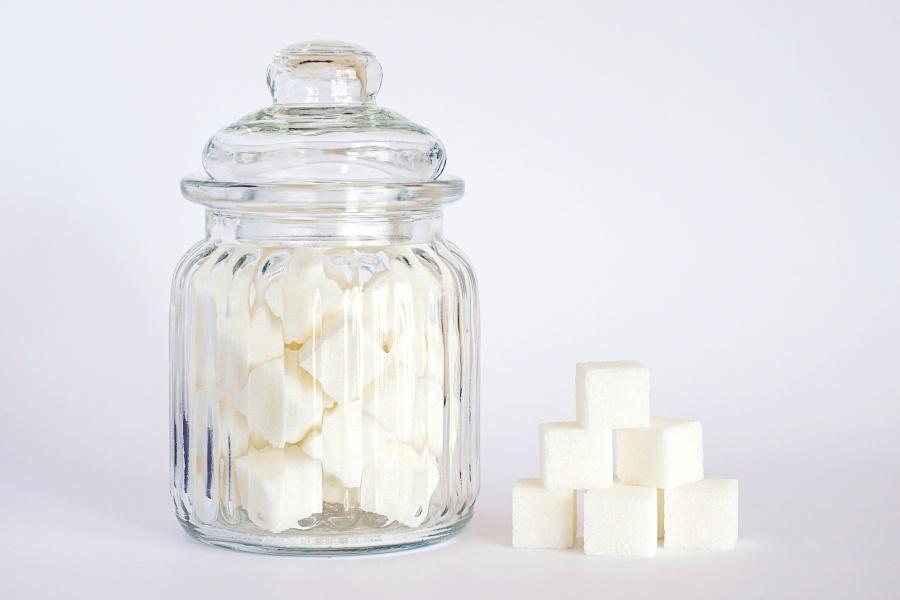 Białe tło. Szklany słoiczek z wieczkiem wypełniony kostkami cukru. Obok kopczyk z kostek cukru.