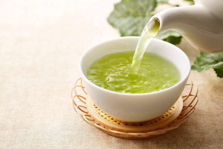 Zielona herbata nalewana z czajniczka do ceramicznej czarki, na wiklinowej podstawce.