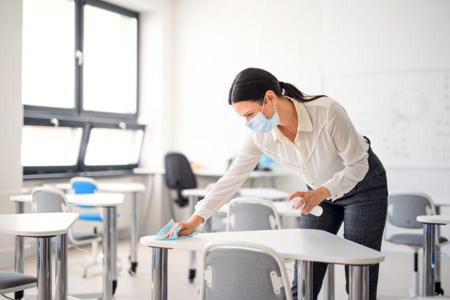 Nauczycielka w maseczce dezynfekuje ławkę w klasie przed rozpoczęciem lekcji.
