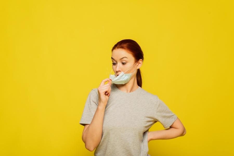 Żółte tło. Kobieta ściąga z twarzy maseczkę jednorazową.